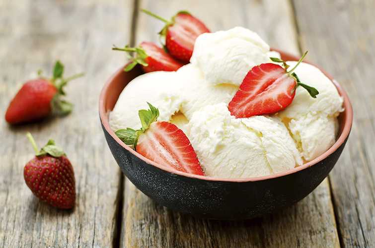 vanilla ice cream with strawberries on a dark wood background. tinting. selective focus